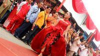 Pedagang pasar memperagakan busana pesta batik nan seksi dalam Peragaan busana batik bertajuk 'Lenggak Lenggok Neng Pasar Segamas', Purbalingga. (Liputan6.com/Dinkominfo PBG/Muhamad Ridlo)