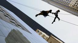 """Sepasang penari melakukan aksi tarian diantara gedung, Manhattan borough New York (19/4). Aksi nekat ini merupakan bagian dari pembukaan toko """"Hublot""""di Fifth Avenue, Manhattan. (REUTERS/Andrew Kelly)"""