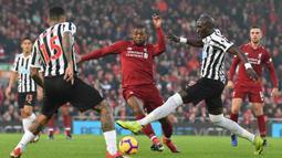 Gelandang Liverpool, Georginio Wijnaldum, berusaha melewati kepungan pemain Newcastle pada laga Premier League di Stadion Anfield, Liverpool, Rabu (26/12). Liverpool menang 4-0 atas Newcastle. (AFP/Paul Ellis)