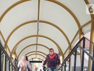Warga melitasi Jembatan Penyeberangan Orang (JPO) di depan Stasiun Pasar Minggu, Jakarta, Kamis (9/1/2020). JPO yang juga dilengkapi dengan penutup dan lampu warna-warni tersebut menghubungkan Stasiun Pasar Minggu dengan pasar tradisional Pasar Minggu. (Liputan6.com/Immanuel Antonius)