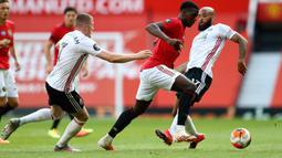 Gelandang Manchester United, Paul Pogba (tengah) berusaha mengontrol bola dari kawalan pemain Sheffield United John Lundstram dan David McGoldrick pada pertandingan lanjutan Liga Inggris di Old Trafford, Inggris (24/6/2020). MU menang telak 3-0 atas Sheffield United. (Michael Steele/Pool via AP)