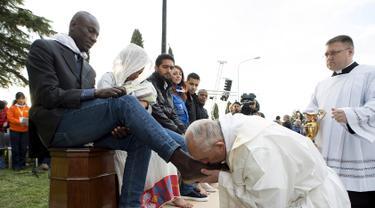 Paus Fransiskus mencium kaki imigran sebelum memimpin misa Kamis Putih, di sebuah lokasi penampungan di Castelnuovo, dekat Roma, Italia, Kamis (24/3/2016). (Reuters/ Osservatore Romano)