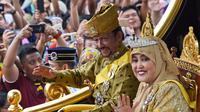 Sultan Hassanal Bolkiah dan Ratu Saleha Brunei saat naik kereta kerajaan melambaikan tangan kepada warga sekitar selama prosesi Golden Jubilee di Bandar Seri Begawan (5/10). Perayaan tersebut menandai 50 tahun bertahta. (AFP PHOTO / Roslan Rahman)