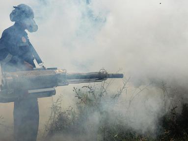 Petugas dari Puskesmas Kecamatan Cengkareng melakukan pengasapan (fogging) untuk membasmi nyamuk Demam Berdarah di Kawasan Kedaung, Jakarta Barat, Selasa (23/4). Pengasapan (fogging) dilakukan sebagai langkah pengendalian vektor nyamuk DBD . (merdeka.com/Imam Buhori)