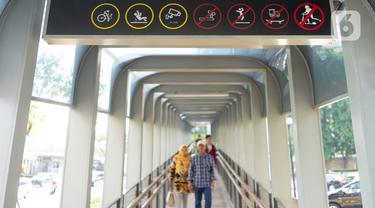 Pejalan kaki lewat di bawah rambu larangan untuk skuter listrik melintas yang terpasang di Jembatan Penyeberangan Orang (JPO) Bundaran Senayan, Jakarta, Jumat (15/11/2019). Rambu tersebut untuk mengantisipasi adanya penguna skuter listrik yang masuk ke JPO. (Liputan6.com/Immanuel Antonius)