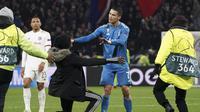 Seorang penggemar berlutut di depan penyerang Cristiano Ronaldo selama pertandingan antara Lyon dan Juventus pada leg pertama babak 16 Liga Champions di Stadion Olimpiade Lyon di Decines, Prancis (26/2/2020). Dalam pertandingan ini Lyon berhasil mengalahkan Juventus 1-0. (AP Photo/Laurent Cipriani)