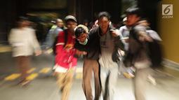 Sejumlah pelajar membantu rekan mereka yang terluka dalam demonstrasi berujung ricuh di Pejompongan, Jakarta, Rabu (25/9/2019). Sebelumnya, ribuan pelajar yang melangsungkan demonstrasi di Gedung DPR terlibat bentrok dengan polisi. (Liputan6.com/Helmi Fithriansyah)