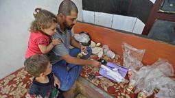 Warga Suriah, Hadheefa al-Shahadh ditemani anak-anaknya saat membuat masker gas untuk menghadapi serangan pasukan pemerintah di Desa Maud Shurin, Provinsi Idlib, Selasa (11/). Cara membuat masker gas dia pelajari dari Youtube. (OMAR HAJ KADOUR/AFP)