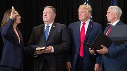 Gina Haspel (kiri) diambil sumpahnya sebagai Direktur CIA yang baru disaksikan oleh Presiden AS Donald Trump dan Wakil Presiden AS Mike Pencedi markas besar CIA, Virginia, Senin (21/5). (AFP PHOTO/SAUL LOEB)