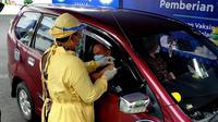 Seorang warga lanjut usia (lansia) di Kota Malang disuntik vaksin Covid-19 di layanan sistem drive thr yang digelar satu hari saja bertepatan dengan HUT ke-107 Kota Malang pada 1 April 2021 (Liputan6.com/Zainul Arifirin)