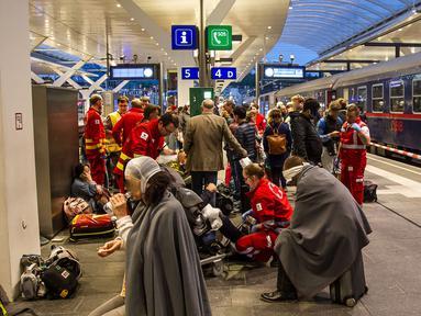 Petugas penyelamat menangani penumpang kereta yang terluka akibat dua gerbong kereta bertabrakan di stasiun kereta api utama di Salzburg, Austria (20/4). Sedikitnya 40 orang mengalami luka-luka dalam insiden ini. (FMT/Wolfgang Moser/APA/AFP)