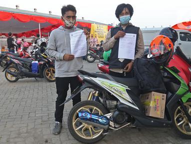 Pengendara motor menunjukkan hasil pemeriksaan tes Swab antigen di pos pemeriksaan kesehatan, Cikarang, Kabupaten Bekasi, Sabtu (22/5/2021). Ada 14 orang dari 4.406 pengendara motor yang terindikasi positif COVID-19 pada arus balik tanggal 16-22 Mei 2021. (Liputan6.com/Herman Zakharia)