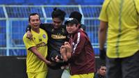 Kiper Arema FC, Kurniawan Kartika Ajie, harus digendong keluar lapangan saat latihan perdana Singo Edan berlangsung di Stadion Kanjuruhan, Malang, Senin (3/8/2020). (Bola.com/Iwan Setiawan)