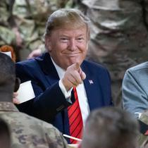 Presiden Amerika Serikat Donald Trump menunjuk sambil makan bersama para tentara di Pangkalan Udara Bagram, Afghanistan, Kamis (28/11/2019). Kunjungan dadakan Trump pada hari Thanksgiving tersebut mengejutkan pasukan AS yang bertugas di Afghanistan. (AP Photo/Alex Brandon)