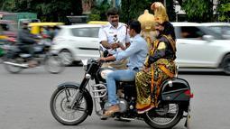 """Polisi memberi mawar kepada pengendara motor tanpa helm yang membonceng seniman berpakaian seperti """"Yamaraj"""", dewa kematian Hindu saat  kampanye 'Road Safety Week' di Bangalore (10/7). (AFP Photo/Manjunath Kiran)"""