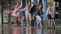 Warga melintasi banjir yang merendam Jalan RA Kartini, Bekasi, Jawa Barat, Kamis (2/1/2020). Banjir yang merendam Jalan RA Kartini sejak kemarin melumpuhkan akses kendaraan dan perekonomian warga setempat. (merdeka.com/Iqbal Nugroho)