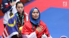 Atlet Taekwondo putri Indonesia, Defia Rosmaniar saat di podium kemenangan Final Women Individual Poomsae di JCC, Jakarta, Minggu (19/8). Defia Rosmaniar meraih emas usai menumbangkan Salahshouri Marjan dari Iran. (Liputan6.com/Helmi Fithriansyah)