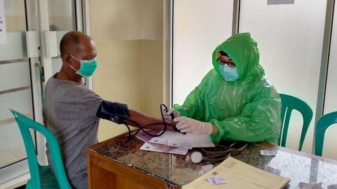 Paramedis Puskesmas Leuwiliang Bogor menggunakan jas hujan plastik untuk mencegah penyebaran virus corona Covid-19. (Rasyid Ali/Merdeka.com)