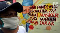 Warga berjalan melintasi mural bertema COVID-19 di kawasan Tanah Tinggi, Tangerang, Banten, Rabu (20/1/2020). Kegiatan ini dalam rangka mensosialisasikan bahaya penyebaran COVID-19 kepada warga pengguna jalan umum. (merdeka.com/Arie Basuki)