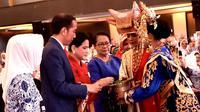 Presiden Joko Widodo dan Ibu Negara Iriana saat menghadiri pembukaan Rakernas IWAPI XXVIII di Padang, Sumatera Barat, Senin (8/10). Jokowi mendorong para pengusaha perempuan memasarkan produknya ke pasar mancanegara. (Liputan6.com/Pool/Biro Pers Setpres)