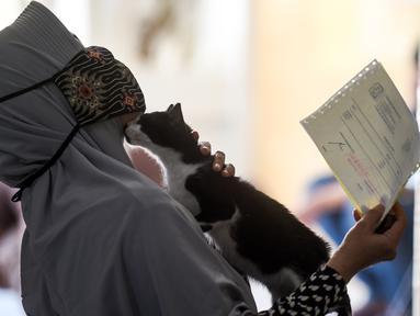 Seorang wanita yang mengenakan masker terlihat bermain dengan seekor kucing di ruang tunggu Rumah Sakit Hewan Jakarta (RSHJ) di Ragunan, Jakarta (22/9/2020). Didirikan pada 1993, RSHJ merupakan salah satu rumah sakit hewan tertua di Indonesia. (Xinhua/Agung Kuncahya B.)