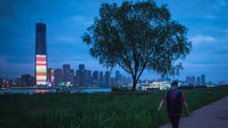 Seorang warga berjalan di Taman Jiangtan Hankou di Wuhan, Provinsi Hubei, China tengah, pada 26 Maret 2020. Seiring meredanya wabah virus corona (Covid-19), kehidupan di Wuhan berangsur-angsur kembali normal. (Xinhua/Xiao Yijiu)