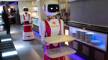 Leah Hu (kiri) menunjukkan penggunaan robot pengganti pelayan sebagai bagian dari uji coba langkah-langkah aturan jaga jarak di restoran keluarga Royal Palace, Belanda, 27 Mei 2020. Robot ini bertugas menyapa pelanggan, menyajikan makanan dan minuman dan mengembalikan alat makan. (AP/Peter Dejong)