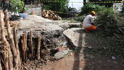 Jalan yang ambles di Jalan Al-Mujahidin, Cipinang, Pulogadung, Jakarta Timur, Rabu (21/2). Jalan tersebut ambles karena tidak kuat menahan beban truk besar yang sering melintas di jalan tersebut. (Liputan6.com/Arya Manggala)