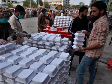 Relawan menyiapkan kotak makanan dan minuman manis tradisional orang-orang berbuka puasa, di Rawalpindi, Pakistan, Minggu, (3/5/2020). Umat Muslim di seluruh dunia sedang melaksanakan Ramadan untuk menahan diri dari makan, minum sejak subuh sampai senja. (AP/Anjum Naveed)