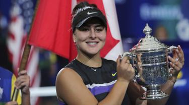 Petenis Kanada, Bianca Andreescu (19) tersenyum saat berpose dengan Piala AS Terbuka 2019 usai mengalahkan Serena Williams dari AS di final tunggal putri di New York (7/9/2019). Andreescu menang atas Serena 6-3, 7-5. (AP Photo/Charles Krupa)