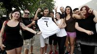 Suporter memegang jersey Juventus atas nama Cristiano Ronaldo saat merayakan transfer sang megabintang di Turin, Selasa (10/7). Juventus mendatangkan Ronaldo dengan biaya 100 juta euro atau Rp 1,68 triliun. (AFP PHOTO / Isabella Bonottovv)