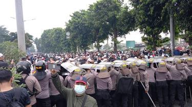 Polisi menghalau simpatisan Rizieq Shihab yang melempari batu di Jalan I Gusti Ngurah Rai, Jakarta. (Merdeka.com/Bachtiarudin Alam)