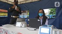 Petugas dites dengan GeNose C19 di Terminal Kampung Rambutan, Jakarta, Minggu (24/1/2021). Menhub akan mengimplementasikan penggunaan GeNose C19 sebagai alat pendeteksi COVID-19 pada calon penumpang di terminal dan stasiun kereta. (Liputan6.com/Herman Zakharia)