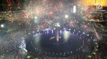 Kembang api menghiasi malam pergantian tahun baru 2018 di kawasan Bundaran HI, Jakarta Senin (1/1/2018). Ribuan warga memadati kawasan tersebut untuk manyaksikan malam pergantian tahun. (Liputan6.com/Angga Yuniar)