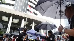 Massa Serikat Pekerja JICT dan FPPI berunjuk rasa di depan Gedung KPK, Jakarta, Selasa (18/12). Massa berunjuk rasa sambil mengenakan payung hitam. (Merdeka.com/Dwi Narwoko)