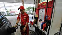 Turunnya harga bahan bakan minyak (BBM) jenis premium membuat kendaraan roda empat ikut mengisinya,  Jakarta, Kamis (1/1/2015). (Liputan6.com/Miftahul Hayat)