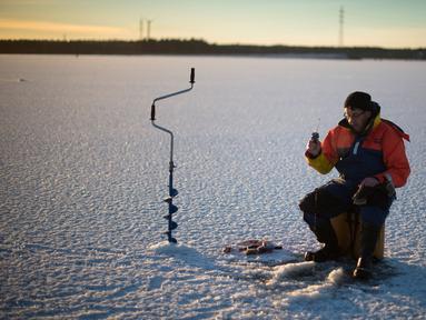 Seorang pria berusaha memancing ikan di laut Bothnia yang sedang membeku, Vaasa, Finlandia (29/12). Kebiasaan memancing di laut beku merupakan hal menantang yang ditunggu-tunggu oleh sebagian warga setempat. (AFP PHOTO/Olivier Morin)