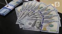Karyawan bank menunjukkan mata uang dolar Amerika Serikat (AS) di Jakarta, Senin (2/11/2020). Nilai tukar rupiah pada perdagangan Senin (2/11) sore ditutup melemah 0,1 persen ke level Rp14.640 per dolar AS, dari perdagangan sebelumnya yaitu Rp14.690 per dolar AS. (Liputan6.com/Angga Yuniar)
