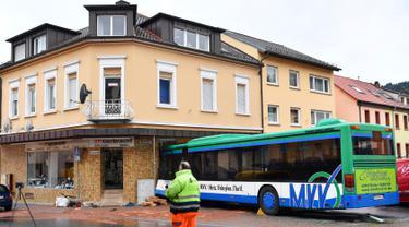 Bus sekolah terparkir di depan bangunan setelah menabrak tembok sebuah toko di Eberbach dekat Mannheim, Jerman, Selasa (16/1). Setidaknya 48 orang terluka dalam kecelakaan bus yang membawa anak-anak sekolah tersebut. (Uwe Anspach/dpa via AP)
