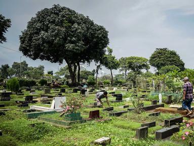 Petugas membersihkan makam yang ada di TPU Karet Bivak, Jakarta, Kamis (4/3/2021). Komisi D DPRD DKI Jakarta meminta kepada Pemprov DKI Jakarta khusunya Dinas Pertamanan dan Hutan Kota untuk menyederhanakan proses izin perpanjangan sewa makam di Jakarta. (Liputan6.com/Faizal Fanani)