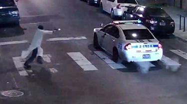 Sebuah gambar yang diambil dari rekaman video CCTV menunjukkan seorang pria bersenjata mendekati mobil polisi yang sedang berpatroli pada jam malam di Philadelphia, Pennsylvania, USA (8/1). (REUTERS/Philadelphia Police Department/Handout)