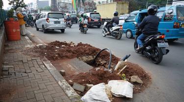 Kendaraan melintas di samping bekas galian proyek yang tidak tuntas pengerjaannya di Jalan Margonda Raya, Depok, Jawa Barat, Kamis (9/5/2019). Kondisi jalan yang diabaikan selama beberapa bulan terakhir tersebut memersempit dan mengganggu aktivitas warga. (Liputan6.com/Immanuel Antonius)