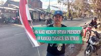 Dengan membawa sebuah tulisan Tasakur Bin Ni'mah, Undang nampak bersemangat melakukan perjalanan panjang dengan jalan menuju istana menemui Presiden Jokowi (Liputan6.com/Jayadi Supriadin)