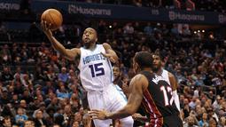 DePemain Charlotte Hornets, Kemba Walker #15 mencoba melakukan layup saat dihadang pemain  Miami Heat,  Rodney McGruder #17 pada laga NBA di Spectrum Center, (29/12/2016). Hornets menang 91-82. (Reuters/Sam Sharpe-USA TODAY Sports)