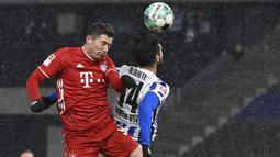 Penyerang Bayern Munchen, Robert Lewandowski dan bek Hertha Berlin, Omar Alderete melompat saat berebut bola dalam ajang Bundesliga 2020/2021 pekan 20 di Olympiastadion, Sabtu (6/2/2021) dini hari WIB. Bayern Munchen menang dengan skor 1-0 atas tuan rumah Hertha Berlin. (John MacDougall/pool via AP)