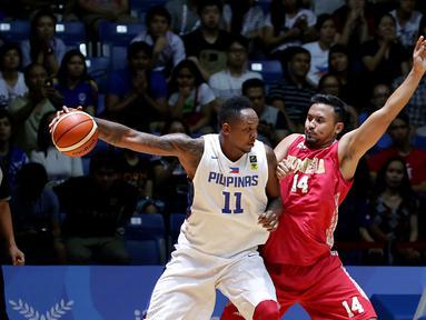 Pebasket Indonesia, Adhi Pratama Prasetyo Putra (kanan) mencoba menghalangi pemain Filipina, Marcus Eugene Douthit di laga final SEA Games ke-28 di OCBC Arena Singapore, Senin (15/6/2015). Indonesia kalah 64-72. (Liputan6.com/Helmi Fithriansyah)