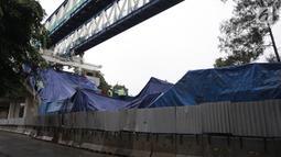 Petugas memeriksa kondisi box girder beton proyek light rapid transit ( LRT)  yang roboh di Kayu Putih, Jakarta Timur, Senin (22/1). Jalur yang roboh di tiang P28-P29 sudah ditutupi dengan terpal biru. (Liputan6.com/Arya Manggala)