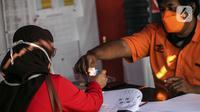Warga menerima uang bantuan sosial (bansos) di kawasan Kedoya Selatan, Jakarta Barat, Rabu (28/7/2021). Bansos berupa uang tunai sebesar Rp 600 ribu tersebut disalurkan oleh PT. Pos Indonesia. (Liputan6.com/Johan Tallo)