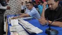 Petugas Rudenim Pekanbaru memperlihatkan pasport yang digunakan imigran Bangladesh untuk ke Indonesia. (Liputan6.com/M Syukur)