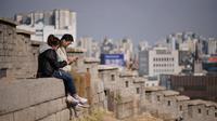 Suami istri melihat ponsel mereka ketika mereka duduk di lereng bukit yang menghadap ke cakrawala kota di Seoul, Korea Selatan (2/4). Korea Selatan sedang bersiap untuk meluncurkan jaringan seluler 5G pertama di dunia pada 5 April. (AFP Photo/Ed Jones)